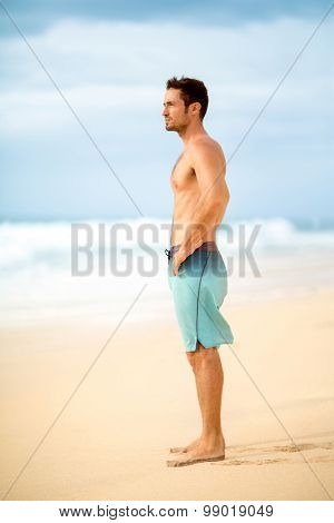 Handsome muscular man standing on the beach and looking thoughtfully into the distance