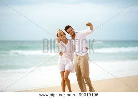 Happy loving couple enjoying vacation together having fun on the beach taking selfie photo using smartphone camera