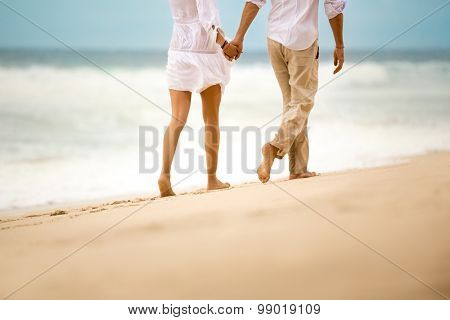Barefoot couple walking on sandy beach