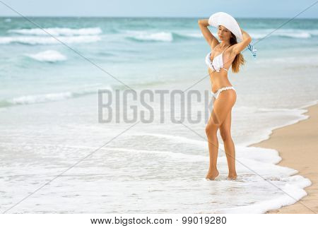 Young sexy woman in white bikini standing in waves on beach