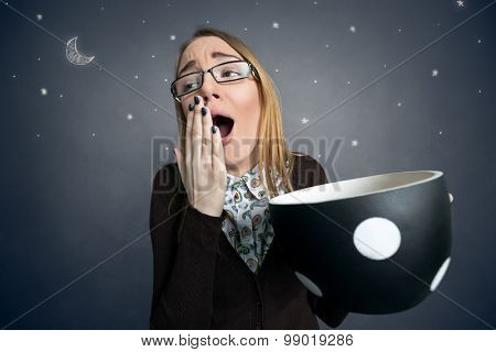 tired female student yawning with big cup of coffee