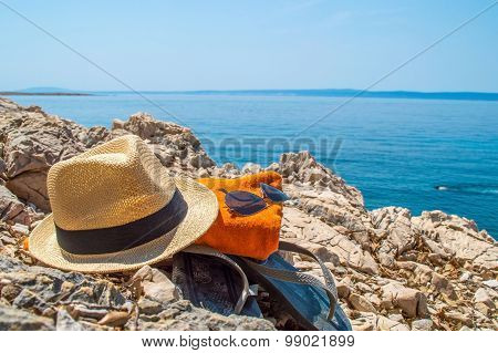 Summer Beach Accessories Left On A Rocky Beach With A Person Swimming In The Sea Or Ocean