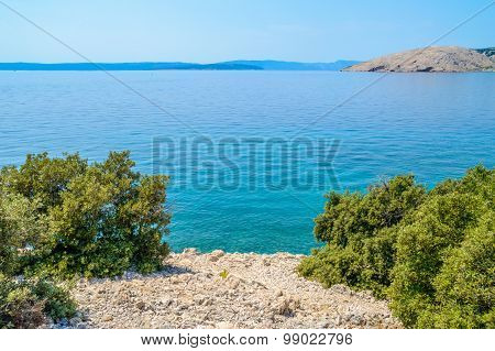 Rocky Coastline With Bushes And Crystal Clear Blue Adriatic Sea With Islands In The Background