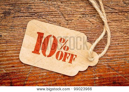 ten percent off discount  - a paper price tag against rustic red painted barn wood