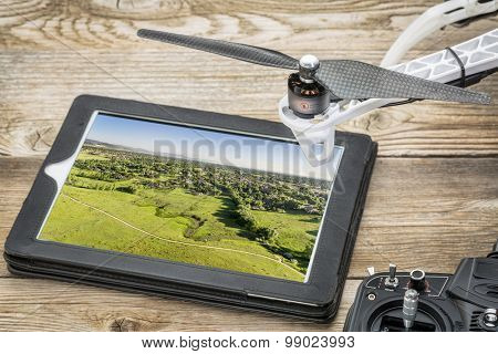 drone aerial photography concept - reviewing aerial picture of Colorado foothills near Fort Collins  on a digital tablet with a drone rotor and radio control transmitter,