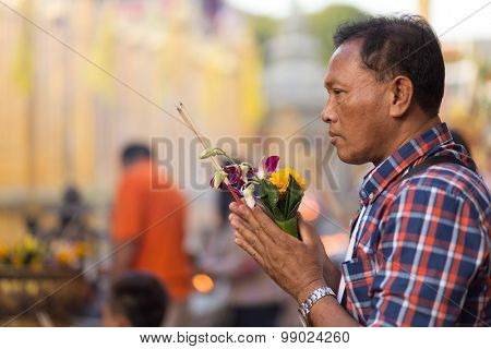 LAMPHUN, THAILAND, DECEMBER 31, 2014: A man holding burning incense sticks and orchid flowers is praying for the new year outside the Buddhist temple of Wat Phra That Hariphunchai in Lamphun, Thailand