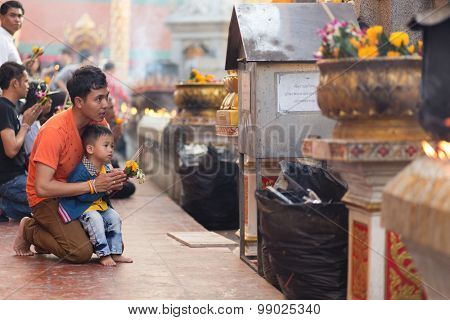 LAMPHUN, THAILAND, DECEMBER 31, 2014: A man and his son are praying for the new year outside the Buddhist temple of Wat Phra That Hariphunchai in Lamphun, Thailand