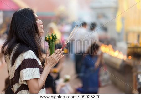 LAMPHUN, THAILAND, DECEMBER 31, 2014: A woman holding burning incense sticks and flowers is praying for the new year outside the Buddhist temple of Wat Phra That Hariphunchai in Lamphun, Thailand