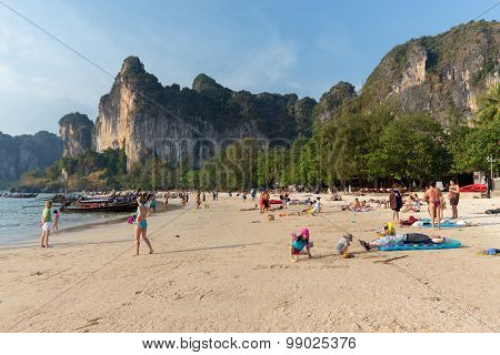 AO NANG, THAILAND, FEBRUARY 10, 2015 : Tourists enjoying the beautiful and wide Railay West beach surrounded by awesome cliffs in Ao Nang, Krabi province, Thailand