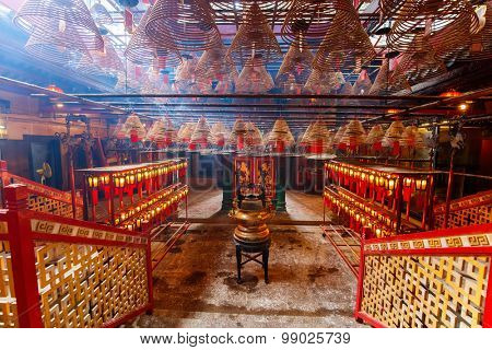 Interior of Man Mo Temple in Hong Kong with incense offerings and coils suspended from the ceiling