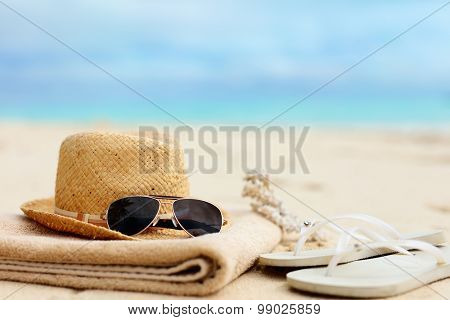 Straw hat, towel, sun glasses and flip flops on a tropical beach