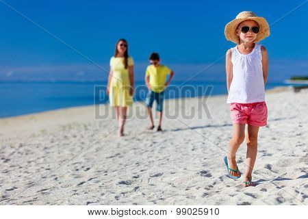 Mother and two kids walking on a tropical beach enjoying summer vacation