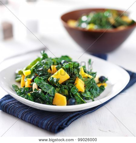 mango and kale salad on white plate