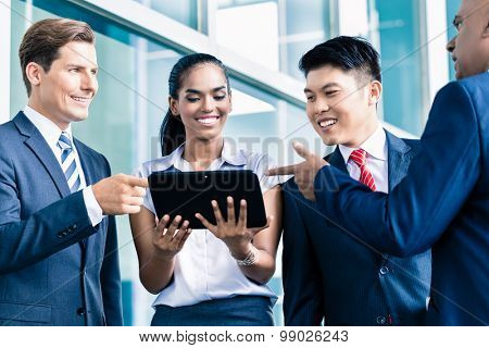 Informal business people with table computer discussing in front of window to the city skyline
