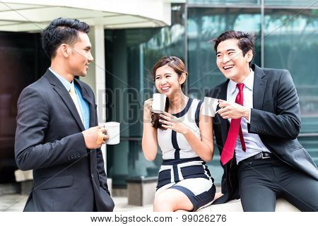 Asian business woman and men having coffee break outside in front of building
