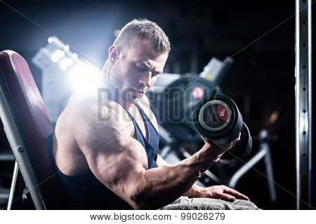 Man at fitness training with dumbbells in gym sitting on a weight bench