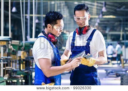 Asian worker team checking work piece in production plant discussing the measurements