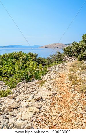 Rocky Coastline With A Foot Path And Bushes And Trees By The Adriatic Sea