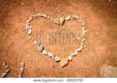 A Heart Made Of Stones On The Red Earth Ground With An Artistic Vignette