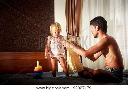 Father Shows New Dress To Little Daughter On Sofa
