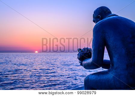 A Statue Of A Man Holding A Sea Shell By The Sea At Sunset