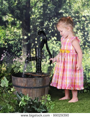 An adorable 2 year old happily pumping water with an old pump on a warm summer day.