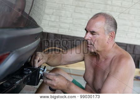 Mechanic Installing Hitch Car