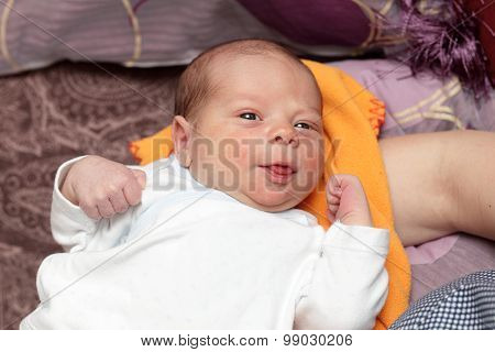 Smiling Newborn Lying On The Blanket