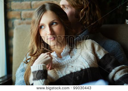Amorous girl with her sweetheart on background