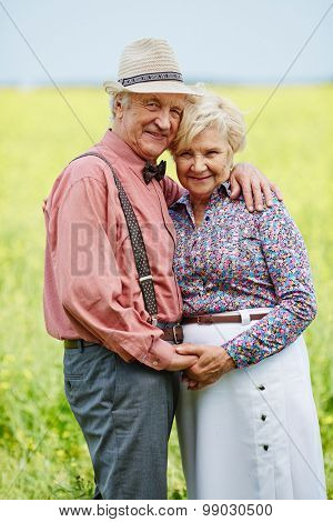 Romantic seniors in embrace looking at camera outdoors