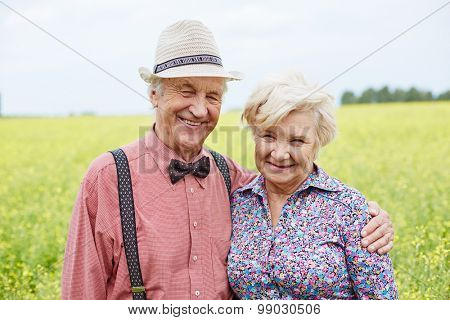 Affectionate and happy seniors looking at camera outdoors