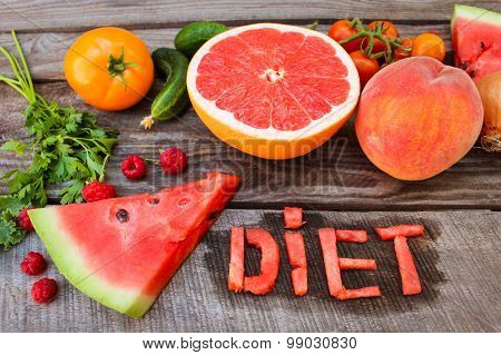 Fruits, vegetables on wooden background. word diet written in English slices of watermelon.