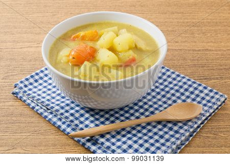 Curry Soup With Potato And Tomato In White Bowl