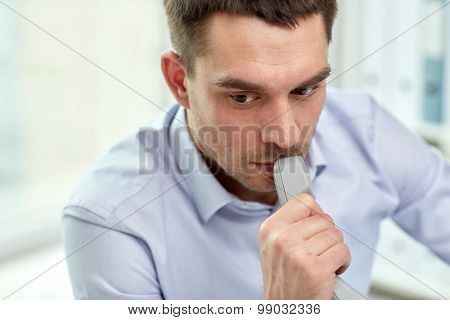 business, people and communication concept - face of businessman with phone receiver in office