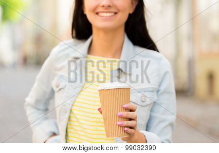 vacation, weekend, takeaway drinks, leisure and friendship concept - close up of happy young woman or teenage girl drinking coffee from disposable paper cups on city street