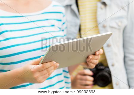 tourism, travel, leisure, holidays and technology concept - close up of women with tablet pc computer and camera outdoors