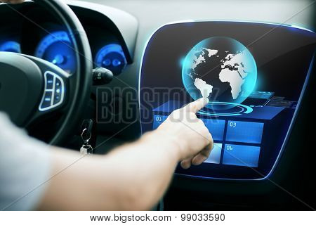 transport, modern technology and people concept - male hand pointing finger to world globe on monitor of car control panel