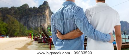 people, homosexuality, travel and love concept - close up of happy male gay couple hugging from back over thailand beach background