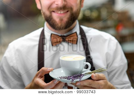 Barista holding cup with coffee