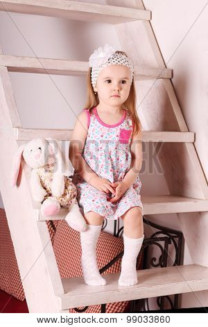Little Cute Blond Girl In Dress Sitting On Wooden Stairs With Soft Toy