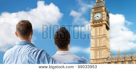 people, homosexuality, same-sex marriage, gay and love concept - close up of happy male gay couple hugging from back over big ben tower in london background