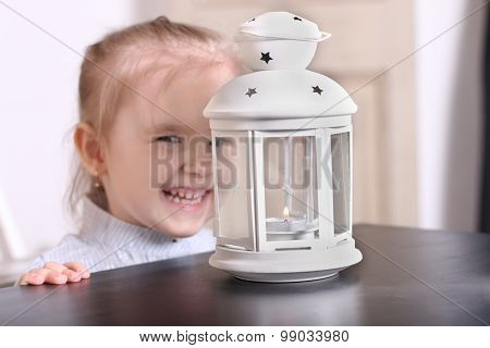 Cute Little Blond Girl Laughing Before Luminaire With Candle. Focus On Lamp