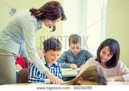 education, elementary school, learning and people concept - teacher helping school kids writing test in classroom
