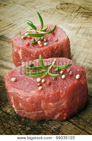 raw steak with pepper and rosemary on the wooden background