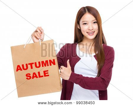 Young Woman hold with shopping bag and thumb up for showing autumn sale