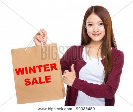 Woman with shopping bag and thumb up for showing winter sale