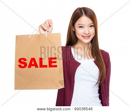 Woman hold with shopping bag and showing a word sale