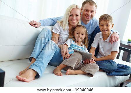 Family of four posing on sofa