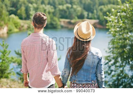 Backs of young dates enjoying natural beauty on summer weekend