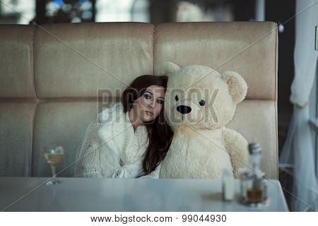 The Sad Girl Sits At A Table With Toy Bear.